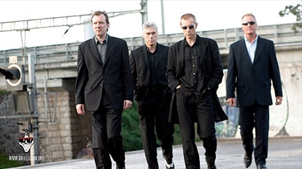 Doctor Feelgood current lineup in suits walkingtowards camera in an urban area